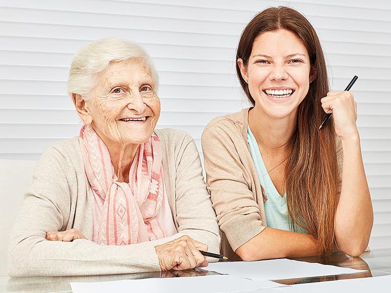 Alte Dame und jüngere Frau lächelnd am Schreibtisch